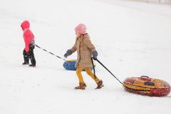 两个女孩照片步行的与管材在冬天公园 免版税库存图片