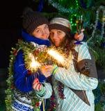 两个女孩用户外圣诞节香槟 库存照片