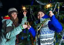 两个女孩用户外圣诞节香槟 免版税库存图片