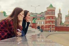 两个女孩画象便衣的在城市,身分和看附近的步行的  图库摄影