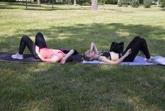 两个女孩疲乏在健身,瑜伽训练以后 免版税图库摄影
