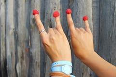两个女孩的手用在木质的背景的莓莓果 图库摄影