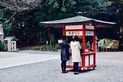 两个女孩祈祷在一个寺庙在日本鹿儿岛 图库摄影