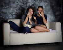 两个女孩神色电视 库存照片