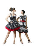 两个女孩穿戴了仿照在看彼此的白色背景的画报样式 免版税库存照片