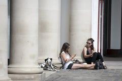 两个女孩简而言之是坐,倾斜反对柱子在剧院附近在科文特花园 达尔马希亚狗在旁边坐 免版税库存图片
