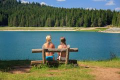 两个女孩背面图坐长凳在山的湖附近 免版税库存照片