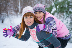 两个女孩获得乐趣在冬天 免版税库存图片