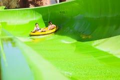 两个女孩获得乐趣在度假在幻灯片的在水公园, 库存图片