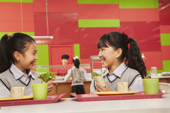 两个女孩谈话在午餐在学校食堂 免版税库存照片