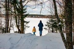 两个女孩通过冬天森林走到湖 图库摄影