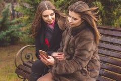 两个女孩采取与智能手机的selfie 免版税库存图片