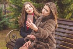 两个女孩采取与智能手机的selfie 库存照片