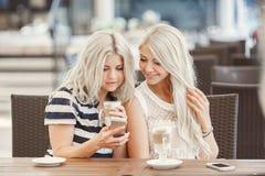 两个女孩饮料咖啡和使用电话 免版税图库摄影