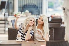 两个女孩饮料咖啡和使用电话 图库摄影