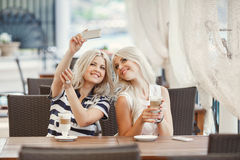 两个女孩饮料咖啡和使用电话 库存照片