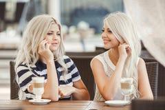 两个女孩饮料咖啡和使用电话 免版税库存照片