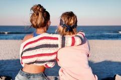 两个女孩,最好的朋友一起坐海滩在s 免版税库存照片