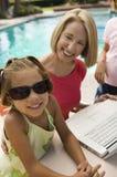 两个女孩(7-9)使用有祖母的膝上型计算机由游泳池画象。 免版税库存照片