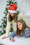 两个女孩给圣诞老人写一封信 库存照片