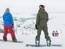 两个女孩(挡雪板)在多雪的背景站立 库存图片