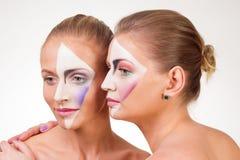两个女孩画象有油漆的在他的面孔 免版税库存照片