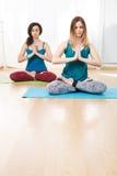 两个女孩画象有眼睛的结束了做瑜伽锻炼 图库摄影