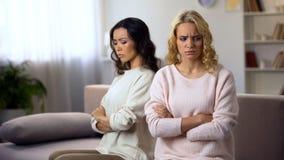 两个女性朋友在家分别地坐沙发,触犯在争吵以后 免版税库存图片