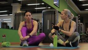 两个女性朋友坐在健身房的木地板在健身类和谈话以后 股票录像