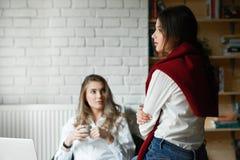 两个女性朋友沟通,运作与膝上型计算机 库存照片