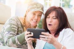 两个女性朋友笑,当使用一个巧妙的电话时 库存照片