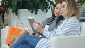 两个女性朋友获得乐趣,当购物在购物中心,有断裂,使用数字式片剂和谈话时 库存照片