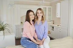 两个女朋友在他们的手上在一次会议上在屋子里 图库摄影