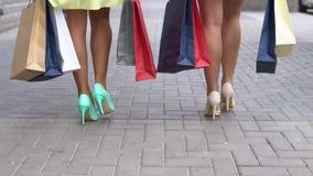 两个女朋友在购物的步行运载不同的颜色包裹与购物的沿着向下街道以后 慢的行动 HD 股票视频