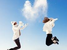 两个女朋友获得乐趣并且享用新鲜的雪 免版税库存照片