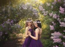 两个女朋友,一个金发碧眼的女人和一个浅黑肤色的男人,充满拥抱的爱 一个美丽的开花的淡紫色庭院的背景 Princ 免版税库存照片