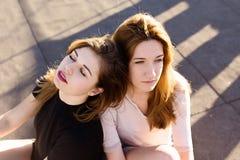 两个女朋友画象屋顶的 免版税库存照片