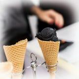两个奶蛋烘饼锥体、卖主的垫铁有球的时髦黑冰奶油和手特写镜头  时髦点心在商店 免版税库存图片