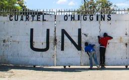 两个好奇男孩在篱芭的孔偷看在盖帽Haitien,海地的联合国总部 免版税库存照片