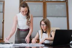 两个妇女商务伙伴在财政决算、统计和文件看 免版税库存照片