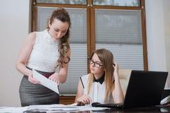 两个妇女商务伙伴在财政决算、统计和文件看 库存照片