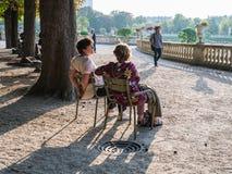 两个妇女朋友在Jardin de Luxembour的公园椅子聊天 免版税库存图片