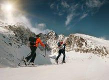 两个妇女滑雪步行者在山上面去  免版税库存照片