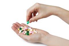 两个妇女的手举行颜色配药药片 免版税库存照片