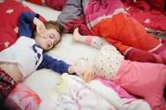 两个妹在床上在晴朗的早晨 库存图片