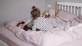 两个妹在床上跳并且跌倒对此 表面微笑 慢的行动 股票视频