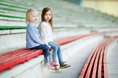两个妹坐体育场位子 库存图片