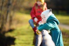两个妹获得乐趣一起在美丽的秋天公园 库存照片