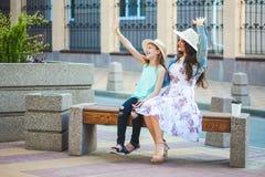 两个姐妹、一个美丽的深色的女孩和女孩步行在城市,坐长凳和谈话,笑并且挥动他们 免版税库存照片