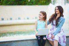 两个姐妹、美丽的深色的走在城市的女孩和女孩,坐通过喷泉和谈,看 免版税库存图片